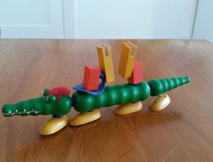 Ergebnis eines Spiel mit den Teilen eines Krokodils, die man unterschiedlich zusammensetzen kann. Dieses Tier hat vier Füße in einer Reihe direkt am Körper und die Teile für die Beine sind auf dem Rücken wie ein Schild.  und